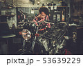 African american woman mechanic repairing a motorcycle in a workshop 53639229