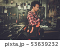 African american woman mechanic repairing a motorcycle in a workshop 53639232