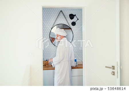 A senior man doing morning routine in bathroom indoors at home. Copy space. 53648614