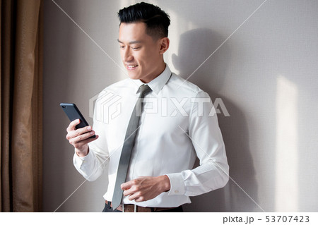 Asian businessman use cellphone 53707423