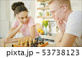 Young african american woman is playing chess with blonde man 53738123