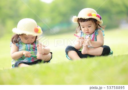 足の裏に落書きする双子 53758895