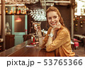 Smiling woman holding martini drink sitting at the bar counter 53765366