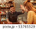 Bearded man giving a high five to a red-haired woman 53765529