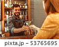 Attractive bartender giving a martini cocktail to a woman 53765695