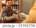 Attractive bar worker handing a martini cocktail to a customer 53765736