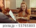 Beaming girl pointing at the menu sitting at bar counter 53765803