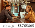 Bewitching woman discussing a menu with handsome dark-haired bearded bartender 53765805