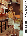 Delightful woman standing at bar and talking on the phone 53765813