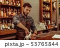 Handsome dark-haired bearded adult bartender polishing glasses at the bar 53765844