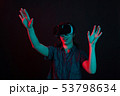 Beautiful caucasian young woman using virtual reality goggles and to watch a movie in studio with 53798634