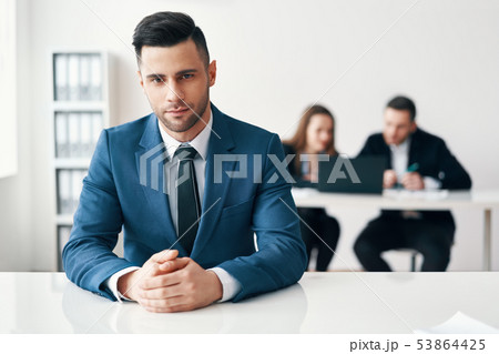 Portrait of confident handsome businessman sitting in office with his business team on background 53864425