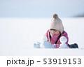 雪原で雪だるまを作る女の子 53919153