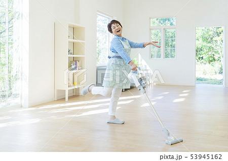 掃除機を持ってポーズをとるシニア女性 53945162