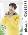 両手でコップを持った笑顔のシニア女性 53945288