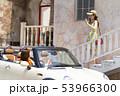 晴天のドライブ日和にオープンカーで迎えに来た友達に笑顔で手を振るワンピースを着た可愛らしい女性 53966300
