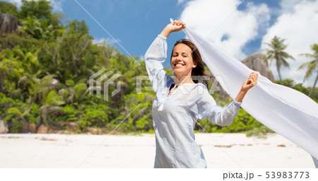 happy woman with shawl waving in wind on beach 53983773