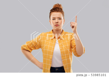 red haired teenage girl pointing finger up 53985101