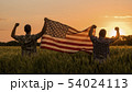 Two men happily raise the American flag over a field of wheat at sunset. 4th of july concept 54024113