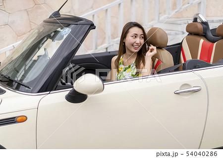 初めてのデートで彼氏のオープンカーの助手席に乗り恥ずかしそうな表情をする可愛い美人女性 54040286