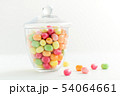 glass jar with candy drops over white background 54064661