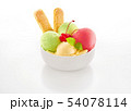 Ice cream scoops decorated with cookies, cherry and mint in bowl on white background 54078114