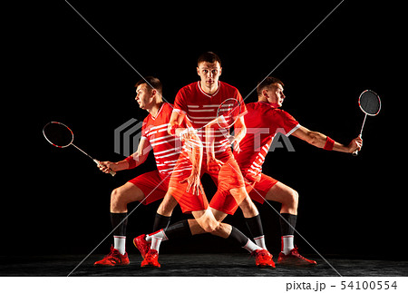 Young man playing badminton isolated on black studio background 54100554
