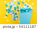 Blue box with confetti on yellow background. 54111187