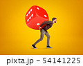 Young man in casual clothes carrying big red casino dice on his back on yellow background 54141225