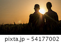 Two men gently hugging at sunset, rear view 54177002