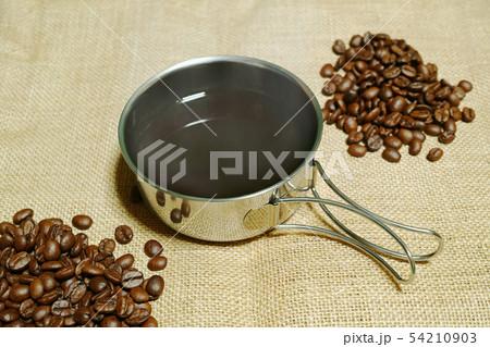 麻の布の上に置いた熱いコーヒーの入ったコッヘルとコーヒー豆 54210903