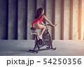 Young healthy woman in red sportswear rides on the exercise bike. Sport and healthy lifestyle 54250356