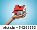 Female hand holding private white house with damaged red roof on blue background 54262533