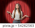Young brunette business woman showing doubt with palms up on red stage curtains background 54262563