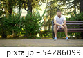 Depressed Sad young man sitting alone on a bench in a summer park. copy space 54286099