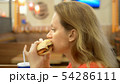 to close. woman with herpes on her lip eats french fries and hamburger 54286111