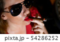 gorgeous woman in red dress with red lipstick on her lips and dark glasses with a cigar on a dark 54286252