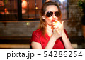 gorgeous woman in red dress with red lipstick on her lips and dark glasses with a cigar on a dark 54286254
