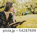 woman with book in springtime park. 54287699