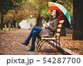 redhead girl sitting at bench in autumn park. 54287700