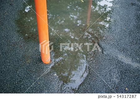 基礎部分が完全に埋まっている鉄棒の支柱と水溜り 54317287