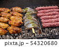 Mixed assortment of marinated meat, chicken, and prawns grilling on hot coals on a BBQ 54320680
