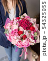 Pink peonies and red hydrangea. Beautiful bouquet of mixed flowers in woman hand. Floral shop 54325955