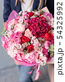Pink peonies and red hydrangea. Beautiful bouquet of mixed flowers in woman hand. Floral shop 54325992
