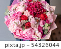 Pink peonies and red hydrangea. Beautiful bouquet of mixed flowers in woman hand. Floral shop 54326044