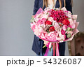 Pink peonies and red hydrangea. Beautiful bouquet of mixed flowers in woman hand. Floral shop 54326087