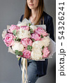 Pink and white peonies in womans hands. Beautiful peony flower for catalog or online store. Floral 54326241