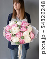 Pink and white peonies in womans hands. Beautiful peony flower for catalog or online store. Floral 54326248