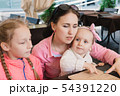Mom with children in the cafe read the menu 54391220