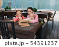 Mom with children in the cafe read the menu 54391237